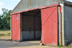 Concrete barn with open doors. Concrete barn with open red doors Royalty Free Stock Photo
