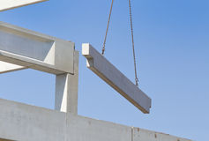 Concrete beam on crane cables in the sky stock photos