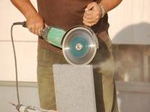 Concrete block cutting. Construction worker cutting concrete block using circular saw stock image