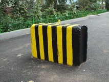 A concrete block with yellow and black stripes Royalty Free Stock Image