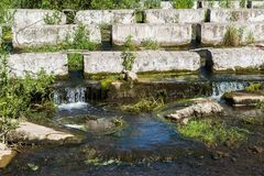 Concrete blocks lying on a small river - dam Stock Images