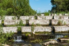 Concrete blocks lying on a small river - dam Stock Photo