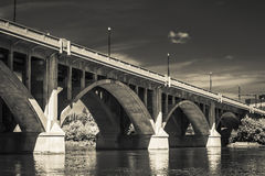 Concrete Bridge. A concrete bridge with visually pleasing arches across the river. Processed with an infrared filter Royalty Free Stock Photography