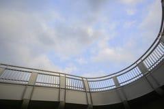 Concrete bridge against the blue cloudy sky. Stock Images