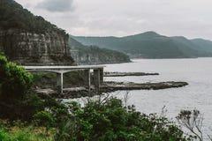 Concrete Bridge Near Mountain Above Shoreline Under Cloudy Sky Royalty Free Stock Photography