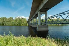 Concrete bridge with underneath walking path. Large concrete bridge crossing the river Dalalven in Avesta, Sweden with path or walk way for pedestrians royalty free stock photography