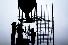 Concrete bucket above workers in construction site Royalty Free Stock Images