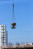 Concrete bucket on blue sky background. Lifting crane delivers c Royalty Free Stock Images