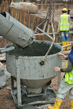 A concrete bucket receiving concrete from concrete truck Royalty Free Stock Photos