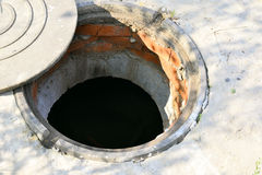 Concrete cesspit with an open hatch on the ground in the summer Stock Photography