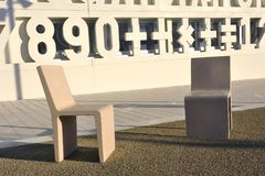 Concrete chairs in front of a modern construction. School Stock Image