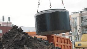 Concrete chamber manhole ring swing on chains over pile of dirt at building site stock video