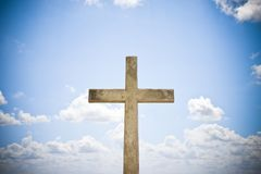 Concrete christian cross against a bright sky - concept image with copy space stock photography