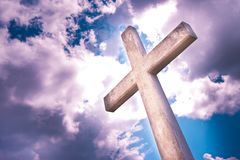 Concrete christian cross against a dramatic cloudy sky - concept royalty free stock images