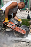 Concrete circular saw. Shot of a construction road worker cutting a paving stone whit a industrial petrol power cutter on a construction site, showing concrete royalty free stock images