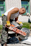 Concrete circular saw. Shot of a construction road worker cutting a paving stone whit a industrial petrol power cutter on a construction site stock photography