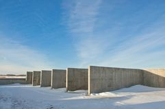 Concrete construction on the background of the winter landscape. Is covered with snow. Frosty sunny day royalty free stock images
