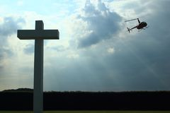 Concrete cross with clouded sky and helicopter. Concrete cross in front. Clouded sky and helicopter in background. Backlighted. Schaffen airfield in Flanders stock photo