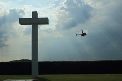 Concrete cross with cloudy sky and helicopter. Concrete cross in front. Cloudy sky and helicopter in background. Backlighted. Schaffen airfield in Flanders stock photo