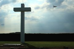 Concrete cross with cloudy sky and sport plane. Concrete cross in front. Cloudy sky and sport plane in background. Backlighted. Schaffen airfield in Flanders royalty free stock image