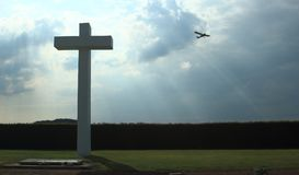 Concrete cross with cloudy sky and sports plane. Concrete cross in front. Cloudy sky and sport plane in background. Backlighted. Schaffen airfield in Flanders royalty free stock image