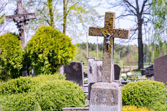 Concrete cross with crucifix in cemetery in summer. Concrete old cross with crucifix in cemetery in summer royalty free stock images