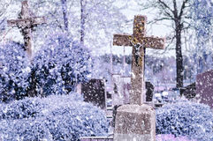 Concrete cross with crucifix in cemetery in winter. Snowfall royalty free stock photos