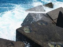 Concrete cubes breakwater with blue crashing waves and surf. In tenerife Royalty Free Stock Image