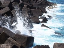 Concrete cubes breakwater with blue crashing waves and surf in t. Concrete cubes forming a breakwater with blue crashing waves and surf in tenerife Stock Images