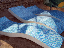 Concrete curving loungers. Concrete curving beach loungers on the beach stock photo