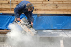 Concrete cutting. Builder cuts edge of concrete slab with diamond saw blade concrete cutter Royalty Free Stock Image