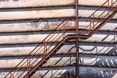 Concrete cylindrical industrial silo with metal stairs with safety railing and large bore pipes. Stock Images