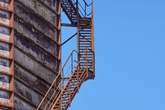 Concrete cylindrical industrial silo with metal stairs with safety railing and large bore pipes. Royalty Free Stock Image