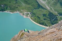 Concrete dam in Alps. Concrete dam of Kaprun power plant and Heinrich-Schwaiger-Haus Royalty Free Stock Images