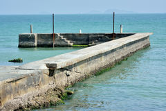 Concrete dam by seaside. Small concrete dam by seaside, shown as devious shape and color comparing between sea water and stone Stock Photography