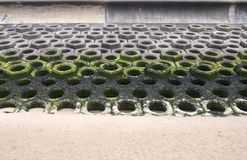 Concrete defensive sea wall on a sandy beach showing seaweed on the high tide mark and precast hexagonal construction Royalty Free Stock Photo