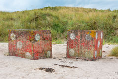Concrete dice on foreshore near Bamburgh England stock photography