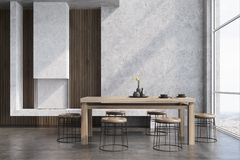 Concrete dining room interior, fireplace. Modern dining room interior with concrete and wooden walls, a wooden table with round chairs near it, a loft window and Royalty Free Stock Photo