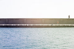 Concrete dock in the ocean. Couple walking on the top. Royalty Free Stock Images