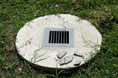 The drainer. A concrete drain hole with steel grille encircled by green grasses Royalty Free Stock Photos