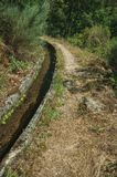 Concrete drainage canal next to dirt path. On rocky terrain covered by bushes and trees at the Serra da Estrela. The highest mountain range in continental stock image