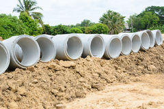 Concrete drainage pipes stacked for construction, irrigation, in Stock Image