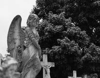 Concrete engel bovenop grafsteen bij begraafplaats Stock Fotografie