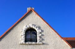 Concrete facade with window in roof attic Royalty Free Stock Photo