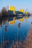 Concrete factory. Silos of a concrete factory reflected in a canal stock photo