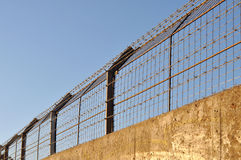 Concrete fence with barbed wire. Against the blue sky Stock Photo