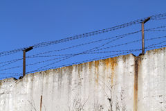 Concrete fence with barbed wire on the background of bright blue. Spring sky Royalty Free Stock Images