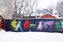 Concrete fence with colored dogs. PERM, RUSSIA - JAN 11, 2014: Concrete fence with colored dogs. In Perm, often hosts exhibitions Street artists Royalty Free Stock Photos