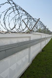 Concrete fence with razor wire Stock Photography