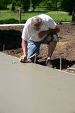 Concrete Finisher with Trowel. Concrete finisher uses a trowel to smooth a freshly poured cement pad Stock Images